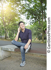 Young asian man talking on mobile phone while sitting