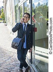 Young asian man talking on mobile phone