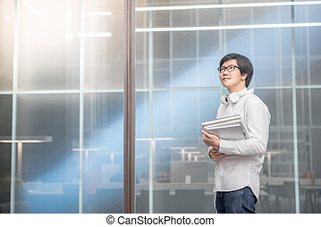 Young Asian man university student holding books in library