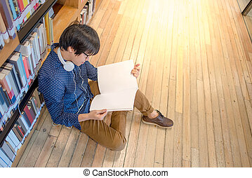 Young Asian man university student in library