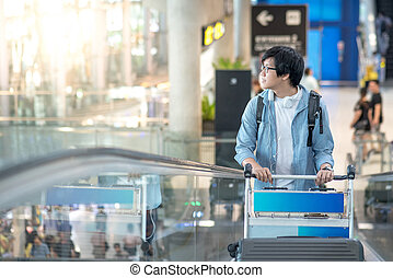 Young Asian man with airport trolley on escalator, walking...