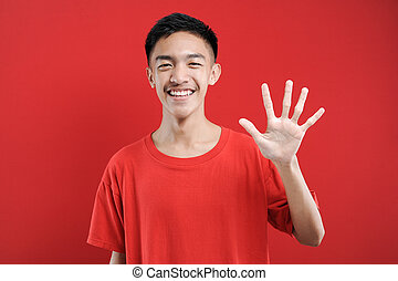 Young Asian man with number five sign finger gesture