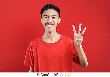 Young Asian man with number three sign finger gesture