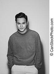 Young asian man's portrait against black background