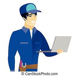 Young asian mechanic using laptop.