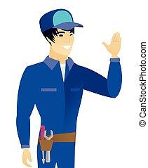 Young asian mechanic waving his hand.