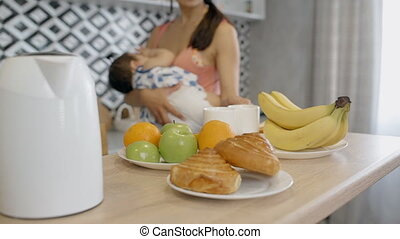 Young asian mother serving the table with her baby on hands.