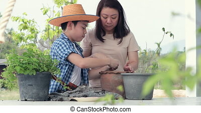 Young asian mother with her boy prepare black soil to little plant on in the garden. Earth day concept.