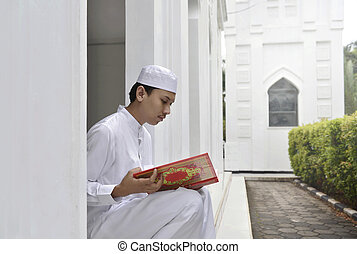 Young asian muslim man reading the holy book Quran