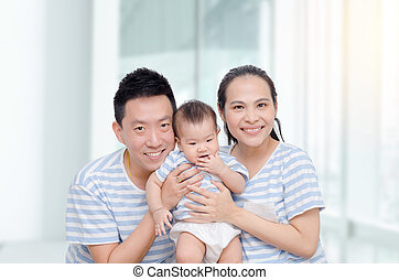 Young asian parent smile with their child at home