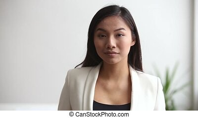 Young asian professional businesswoman looking at camera in office