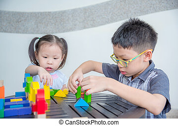 Young Asian sibling play block together at home