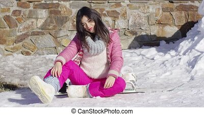 Young asian snowboarder girl relaxing while sitting on snow...