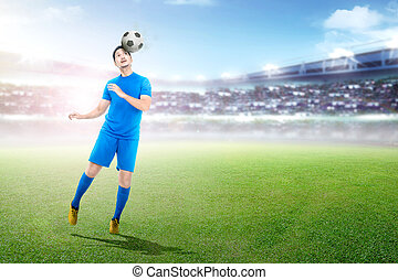 Young asian soccer player heading ball