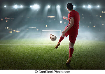 Young asian soccer player shooting the ball