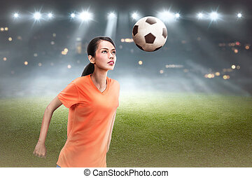 Young asian soccer player woman heading the ball
