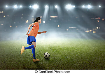 Young asian soccer player woman kick the ball
