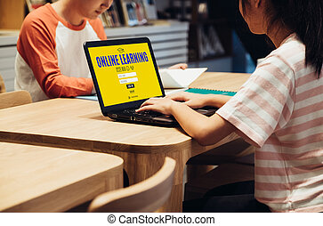 young asian student log in to website online learning center at table in library in school. digital age education concept.