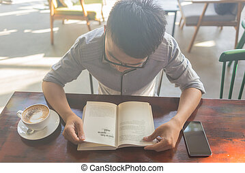 Asian student reading book in the coffee shop