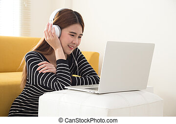 Young Asian student using laptop computer and sitting on floor in living room while listening and watching online coursework with electronic earphones or headphone. Internet E-Learning concept