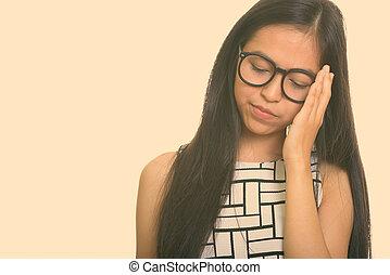 Young Asian teenage nerd girl looking tired
