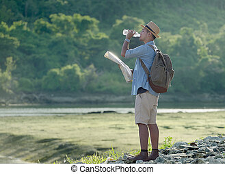Young Asian tourist man with backpack drinking water on nature background
