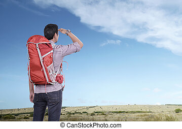 Young asian tourist man with backpack looking at blue sky