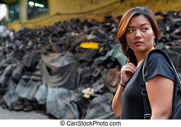 Young Asian tourist woman backpacker thinking and looking back in dirty alley