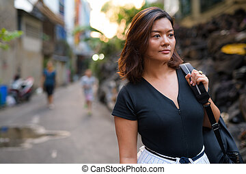 Young Asian tourist woman backpacker thinking in dirty alley