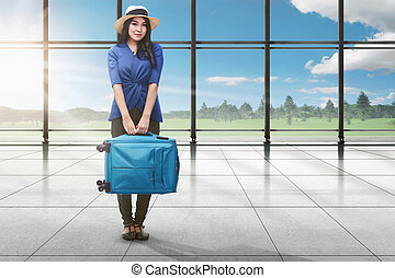 Young asian tourist woman with luggage standing