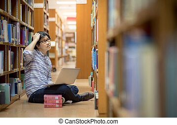 Young Asian university student in library