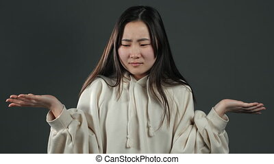 Young asian unsure girl in white hoodie shrugs her arms, makes gesture of I don't know, care, can't help anything. Grey studio background
