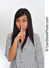 asian woman with her finger raised to her lips