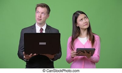 Young Asian woman and young businessman using laptop and digital tablet together