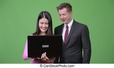 Young Asian woman and young businessman using laptop together