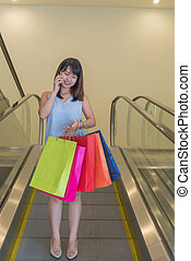 Young Asian woman answer the phone after shopping