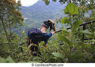 young asian woman backpacker climbing mountain