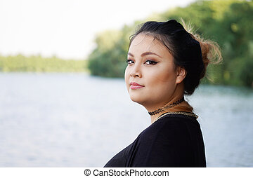 young asian woman by the lake