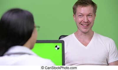 Young Asian woman doctor giving consultation to young man...