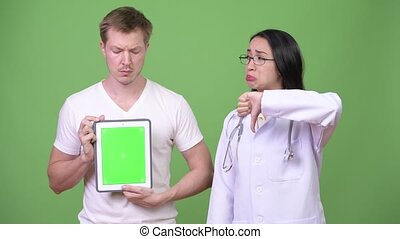Young Asian woman doctor with young man patient showing digital tablet