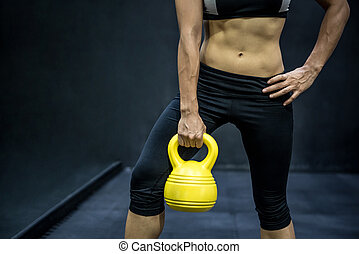 Young Asian woman doing exercise with kettle bell