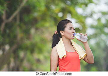Young asian woman drinking water after doing excercise outdoor in a park