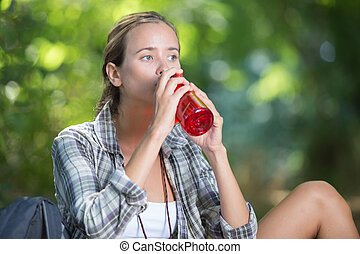 young asian woman drinking water in the forest