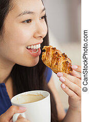 Young asian woman eating a pastry with a cup of coffee