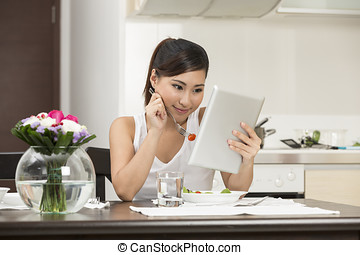 Young Asian woman eating and reading a tablet PC.