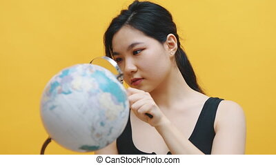 Young asian woman examining the globe with a magnifying glass