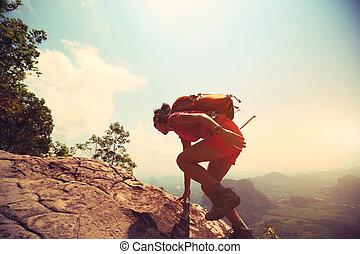young asian woman hiker climbing rock on mountain peak cliff