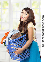 Young asian woman holding a basket full of clothes