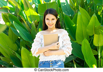 Young asian woman holding a book in the garden