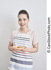 Young asian woman holding plate with homemade chocolate cookies
